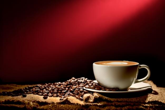 Xícara de café com leite e grãos de café sobre fundo marrom avermelhado