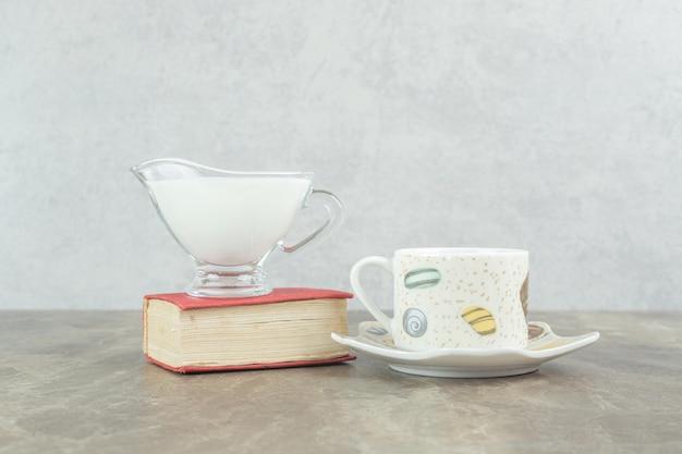 Xícara de café com leite e livro na mesa de mármore.