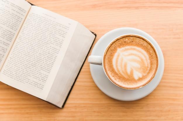Xícara de café com leite em um café cappuccino e livro aberto na mesa