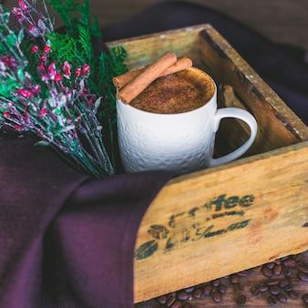 Xícara de café com leite, guarnecida com paus de canela, servida em caixa de madeira com galho de árvore