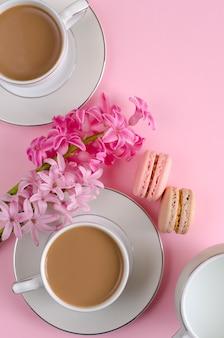 Xícara de café com leite, macaroons, jarra de leite em rosa pastel