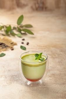 Xícara de café com leite matcha verde com leite, folhas verdes em fundo bege vintage pastel, vista superior, espaço de cópia