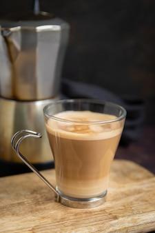 Xícara de café com leite na mesa de madeira e a cafeteira italiana em segundo plano. vertical