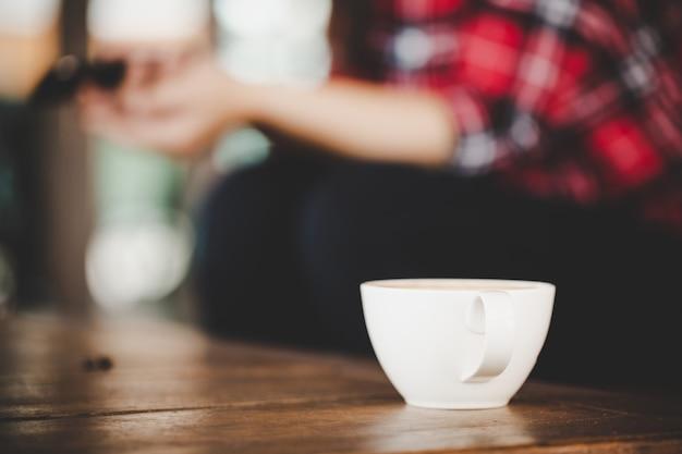 Xícara de café com leite na mesa de madeira no café café