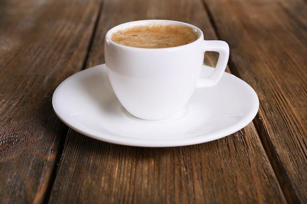 Xícara de café com leite na mesa de madeira