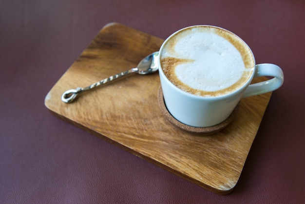 Xícara de café com leite na placa de madeira