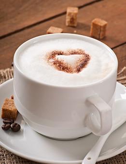 Xícara de café com leite no fundo de madeira velho