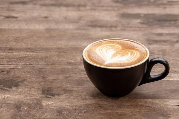Xícara de café com leite preto com coração de espuma em forma de mesa de madeira. copie o espaço para o design do texto.