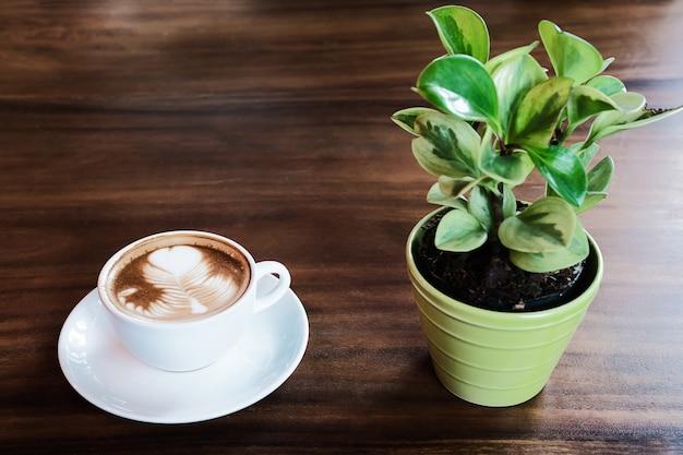Xícara de café com leite quente com pequeno pote de decoração de árvore verde