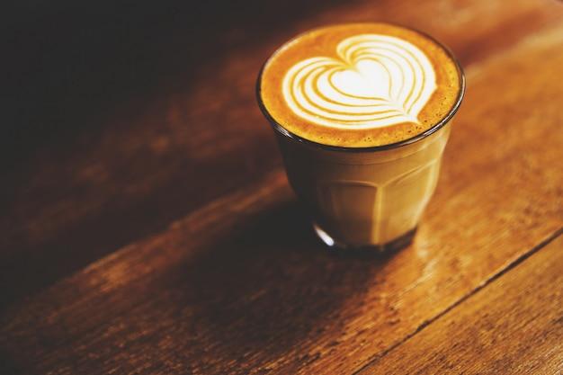 Xícara de café com leite quente é sobre o fundo da mesa de madeira