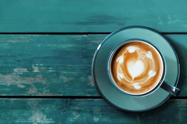 Xícara de café com leite quente na mesa de madeira azul.