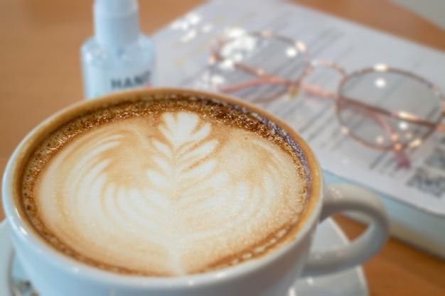 Xícara de café com leite quente na mesa de madeira, fotografia