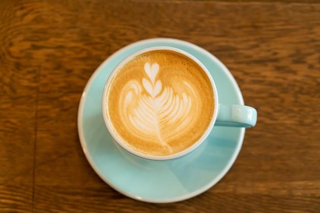 Xícara de café com leite quente na mesa de madeira