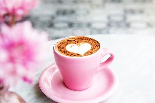 Xícara de café com leite quente no fundo da mesa de mármore com piso de arte