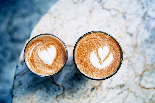 Xícara de café com leite quente no fundo da mesa de mármore