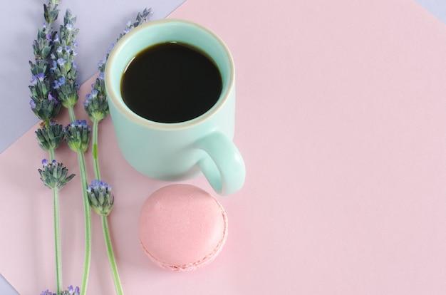 Xícara de café com macaroms e flores de lavanda em fundo violeta e rosa. vista do topo. copie o espaço. postura plana.