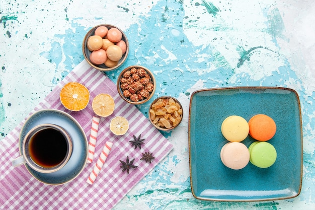 Xícara de café com macarons franceses, passas e confitures no bolo de mesa azul claro