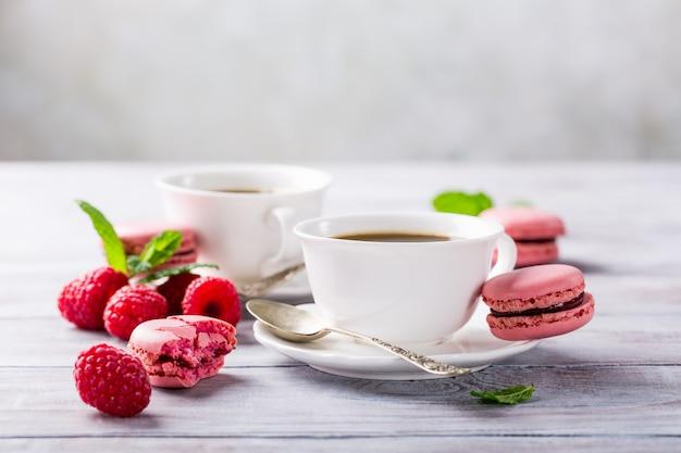 Xícara de café com macaroons de framboesa franceses