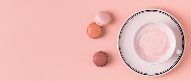 Xícara de café com macaroons em fundo pastel