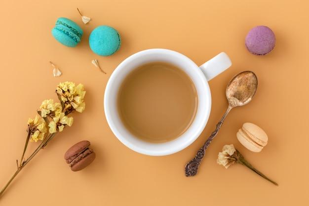Xícara de café com macaroons, flor e colher vintage, lay plana
