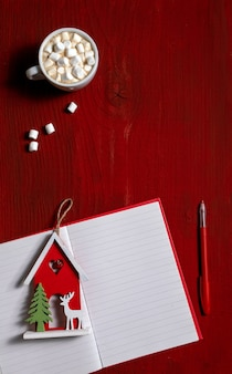 Xícara de café com marshmallow e nota brinquedo de ano novo em fundo vermelho de madeira