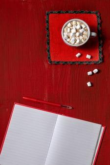 Xícara de café com marshmallow e nota com caneta em madeira vermelha