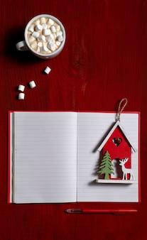 Xícara de café com marshmallow e nota de brinquedo de ano novo em madeira vermelha