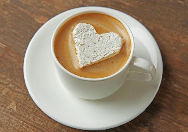 Xícara de café com marshmallow na mesa de madeira