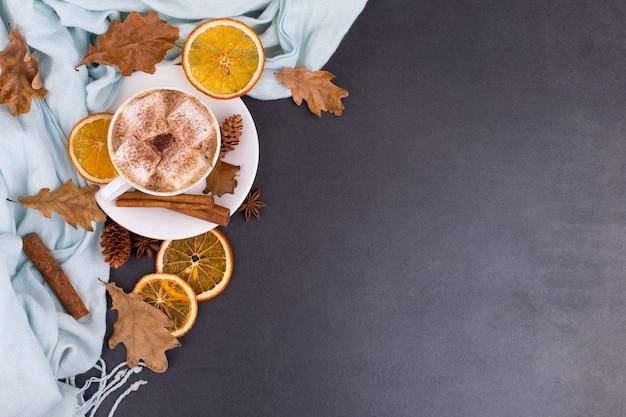 Xícara de café com marshmallows, cacau, cachecol, folhas, laranjas secas, especiarias, sobre fundo cinzento. deliciosa bebida quente de outono, humor de manhã. copyspace.