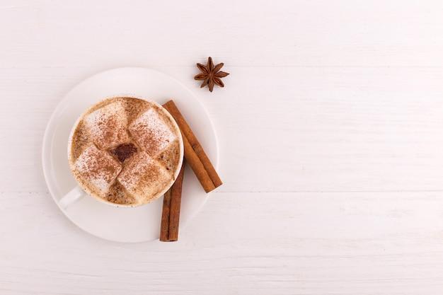 Xícara de café com marshmallows e anis de cacau, canela e estrela, sobre um fundo branco.