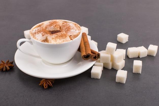 Xícara de café com marshmallows e cacau, açúcar, canela e anis estrelado, sobre um fundo cinza de pedra.