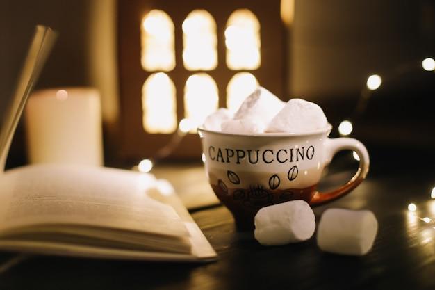 Xícara de café com marshmallows e um livro sobre a mesa. natureza morta em fundo escuro, plano plano