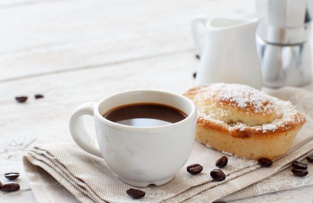 Xícara de café com massa pasticciotto em um fundo rústico close-up