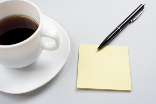 Xícara de café com nota adesiva em branco e caneta isolada em fundo cinza
