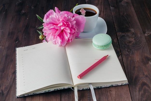 Xícara de café com notebook no fundo de madeira