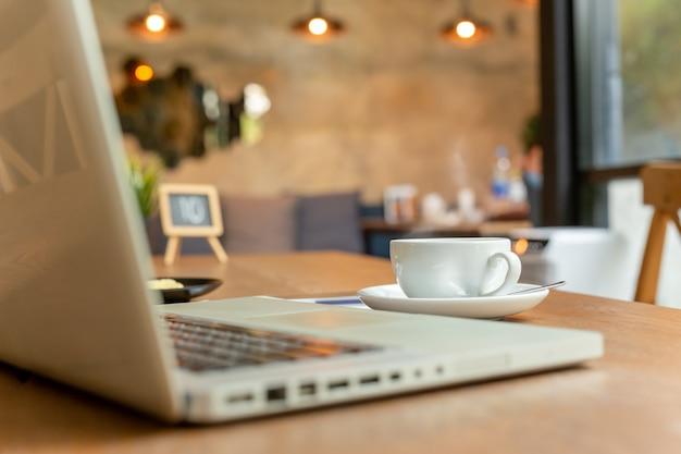 Xícara de café com o portátil na tabela na cafetaria.