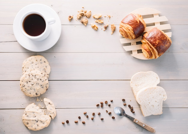 Xícara de café com pães e biscoitos na mesa