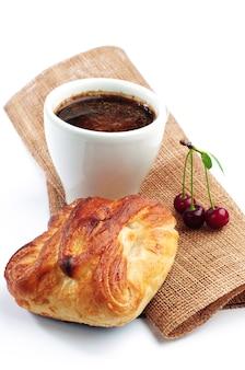 Xícara de café com pão e cereja no branco