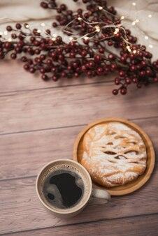Xícara de café com pastelaria na tabela de madeira, luzes de natal, vista superior.