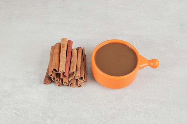 Xícara de café com pau de canela na superfície de mármore.