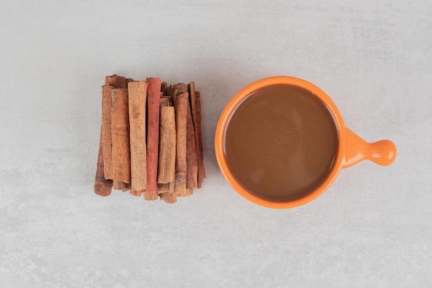 Xícara de café com pau de canela na superfície de mármore