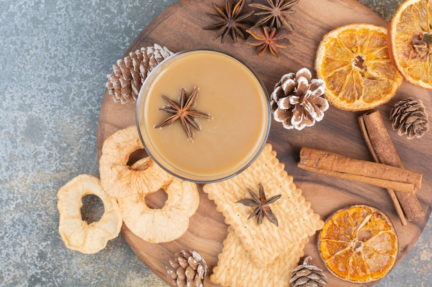 Xícara de café com paus de canela e pinhas na placa de madeira. foto de alta qualidade
