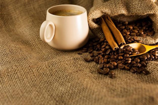 Xícara de café com paus de canela e saco de café na mesa de madeira