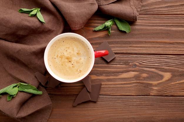 Xícara de café com pedaços de chocolate na mesa