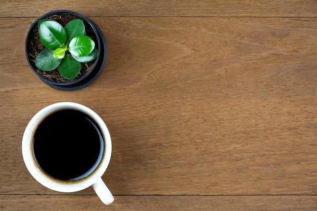 Xícara de café com pequena planta no fundo da mesa de madeira vista superior com espaço de cópia