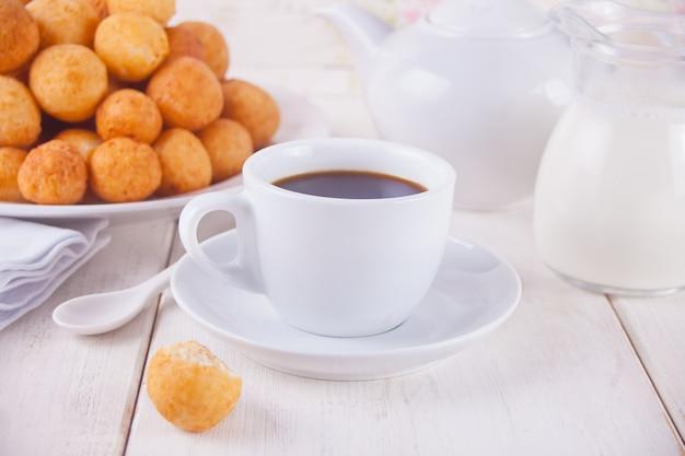 Xícara de café com pequenas bolas de rosquinhas de queijo cottage caseiro recém-assados em um prato em um fundo.