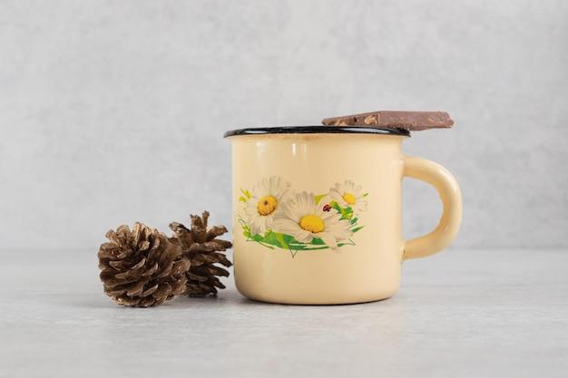 Xícara de café com pinhas e barra de chocolate