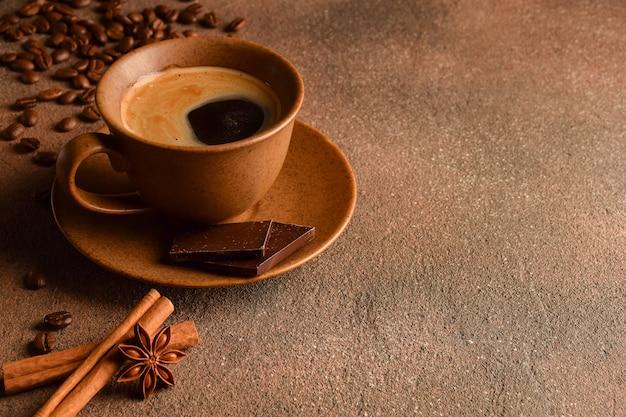 Xícara de café com pires, pedaços de chocolate, grãos de café, canela e erva-doce sobre uma superfície de pedra.
