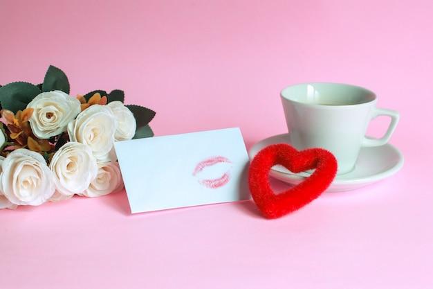 Xícara de café com rosa, beijo marcado em envelope branco e formato de coração isolado em fundo rosa