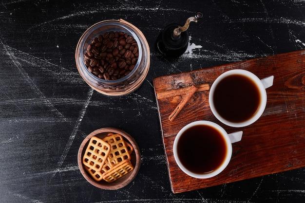 Xícara de café com sabor canela e biscoitos.